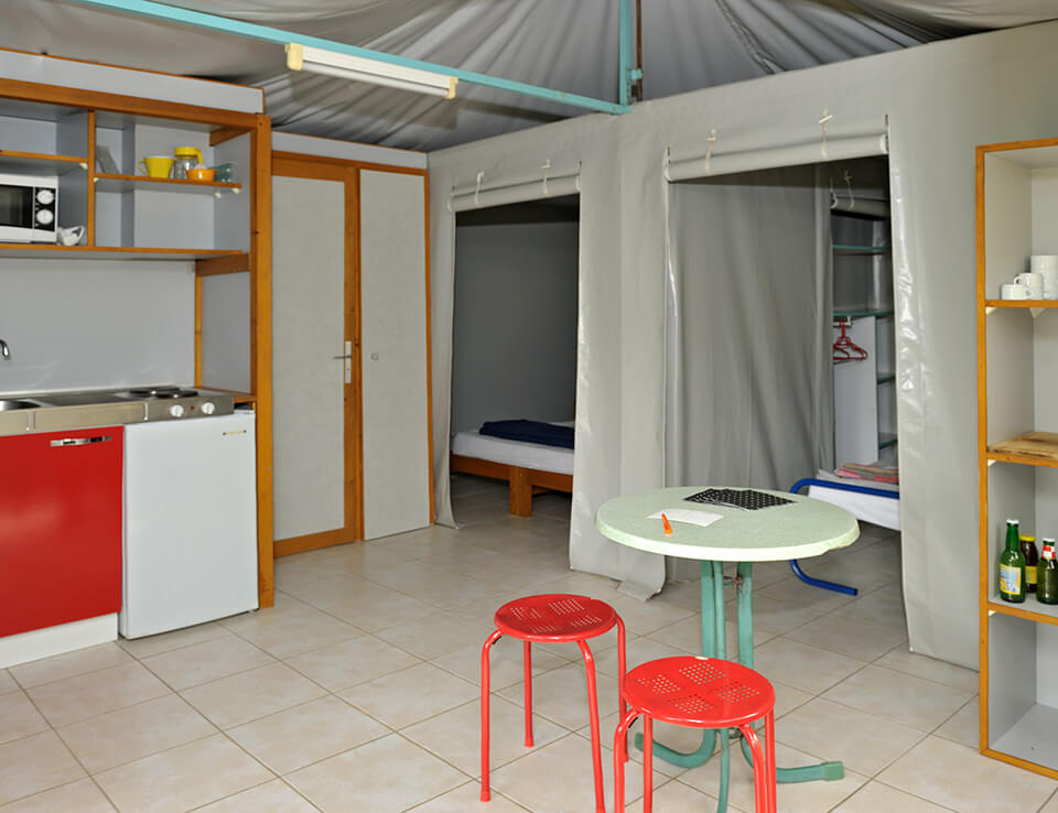 Living part kitchenette of the rigid chalet with auvent Genets in rent out for your holidays at the campsite Parc du Charouzech in Aveyron