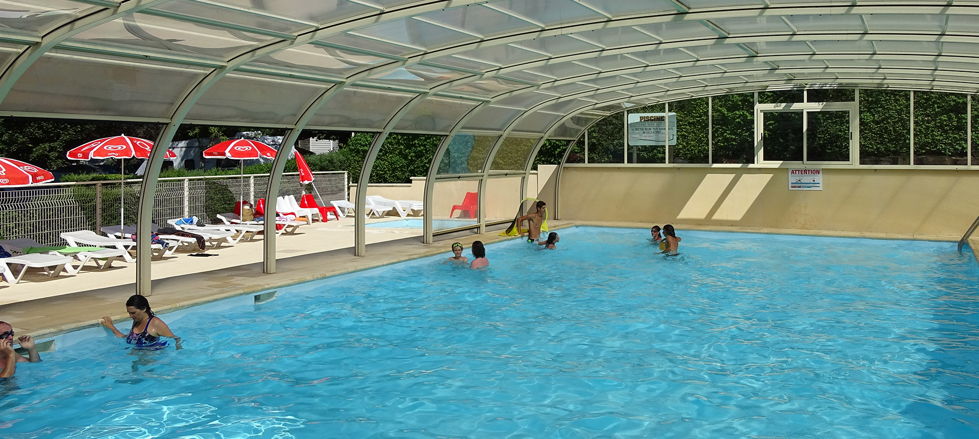 View of the heated swimming pool of tha campsite Parc du Charouzech near the lake in the région Occitanie